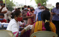 A health worker administers the COVISHIELD vaccine for COVID-19 at a residential area in Ahmedabad, India, Sunday, April 4, 2021. (AP Photo/Ajit Solanki)