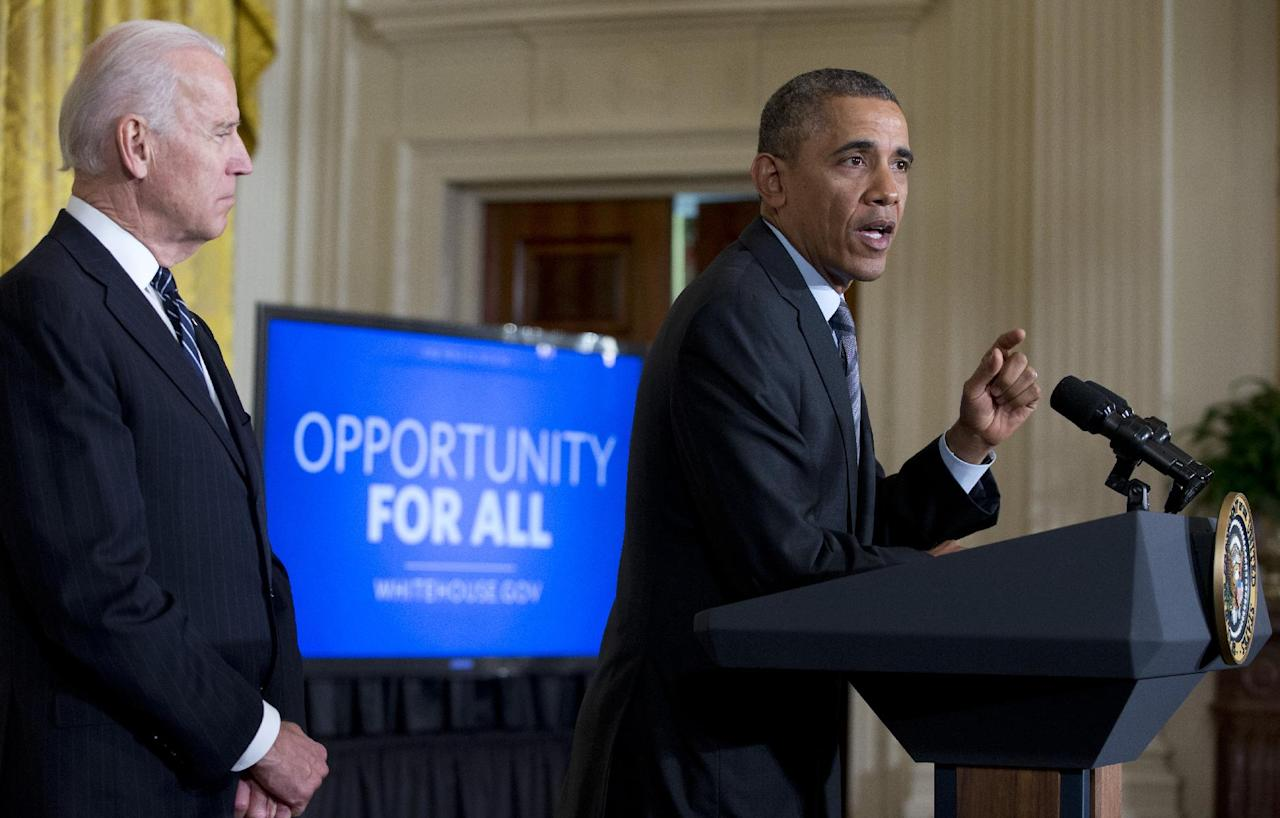 President Barack Obama, with Vice President Joe Biden standing left, gestures as he speaks in the East Room of the White House, Friday, Jan. 31, 2014, in Washington., about helping the long-term unemployed. (AP Photo/Carolyn Kaster)