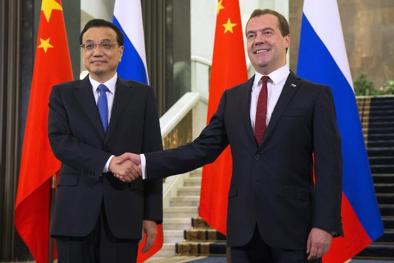 Russia's Prime Minister Dmitry Medvedev (R) welcomes China's Prime Minister Li Keqiang before a meeting in Moscow, on October 13, 2014