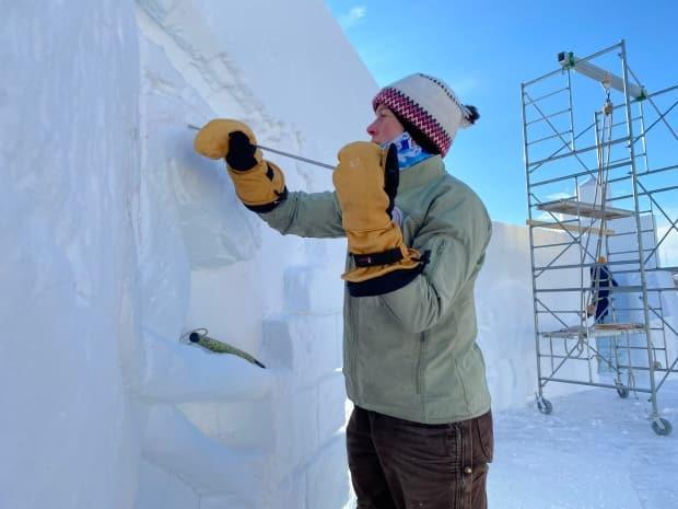 A worker carves details into the walls of Yellowknife's annual snow castle, reinvented this year as an open-air garden.