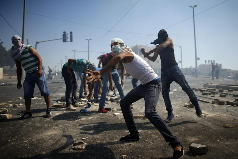 Masked Palestinian protesters throw stones towards Israeli police during clashes in the Shuafat neighborhood in Israeli-annexed Arab East Jerusalem, on July 3, 2014