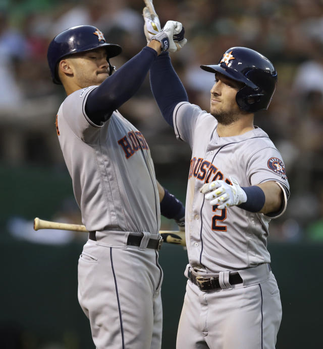 Houston Astros' Alex Bregman, right, celebrates with Carlos Correa after hitting a two-run home run off Oakland Athletics' Mike Fiers during the fourth inning of a baseball game Thursday, Aug. 15, 2019, in Oakland, Calif. (AP Photo/Ben Margot)