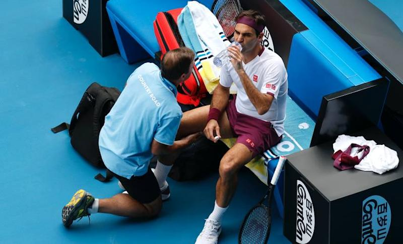 Switzerland's Roger Federer receives treatment from a trainer during his quarterfinal against Tennys Sandgren of the U.S. at the Australian Open tennis championship in Melbourne, Australia, Tuesday, Jan. 28, 2020. (AP Photo/Andy Wong)