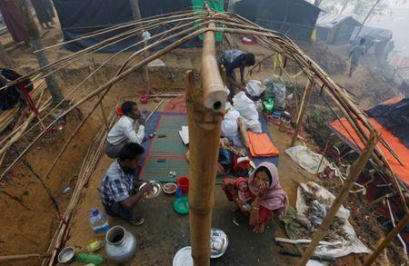 FILE PHOTO: A Rohingya refugee family eats as they sit inside their semi constructed shelter at Kutupalong refugee camp near Cox's Bazar