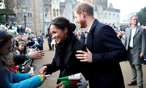 Prince Harry holds Meghan as she smiles with a fan to sign an autograph