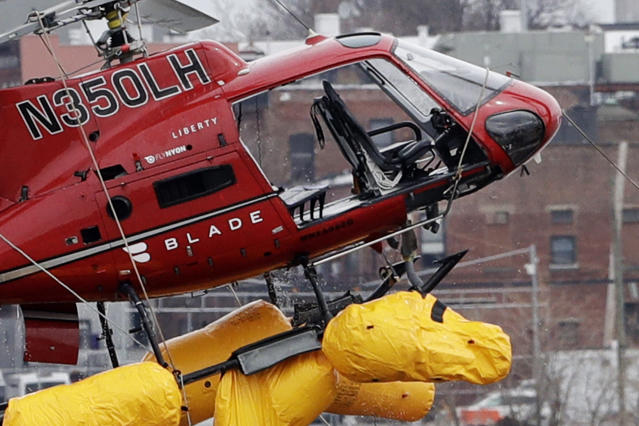 <p>A helicopter is hoisted by crane from the East River onto a barge, March 12, 2018, in New York. The pilot was able to escape the Sunday night crash after the aircraft flipped upside down in the water killing several passengers, officials said. (Photo: Mark Lennihan/AP) </p>