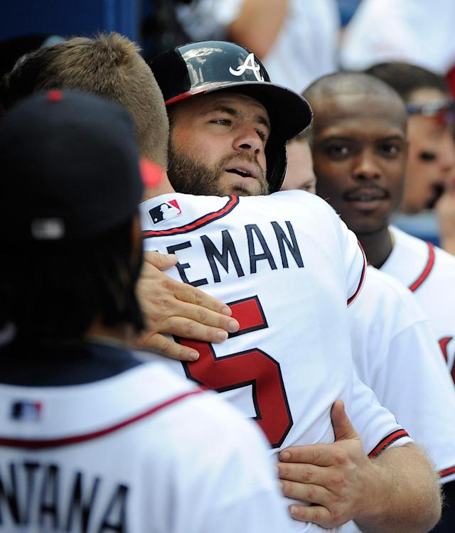 Atlanta Braves' Evan Gattis, center, is congratulated by teammate Freddie Freeman after his solo home run against the San Diego Padres during the seventh inning of a baseball game Monday, July 28, 2014, in Atlanta. (AP Photo/David Tulis)