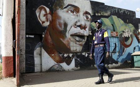 A security guard walks past a wall mural depicting U.S. President Barack Obama outside the Go-Down Art Centre in Kenya's capital Nairobi, July 17, 2015.    REUTERS/Thomas Mukoya
