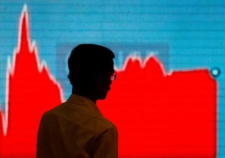 A man walks past a screen displaying news of markets update inside the Bombay Stock Exchange (BSE) building in Mumbai, February 6, 2018. REUTERS/Danish Siddiqui/Files