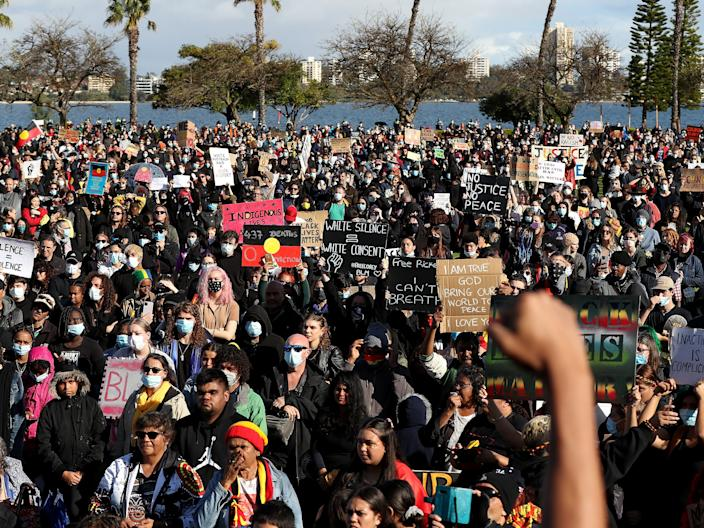 Protesters show their support during the Black Lives Matter Rally at Langley Park on June 13, 2020 in Perth, Australia. The event was organised in solidarity with protests in the United States following the killing of an unarmed black man George Floyd at the hands of a police officer in Minneapolis, Minnesota and to rally against aboriginal deaths in custody in Australia.