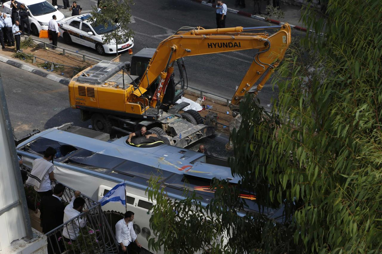 An overturned bus lies next to a construction vehicle at the scene of a suspected attack in Jerusalem August 4, 2014. A Palestinian used his heavy construction vehicle to run down and kill an Israeli and overturn the bus on a main Jerusalem street on Monday in attacks that ended when policemen shot him dead, police said. REUTERS/Siegfried Modola (JERUSALEM - Tags: POLITICS CIVIL UNREST)