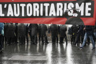"Riot police officers stand behind a banner reading ""authoritarianism"" during May Day demonstration, Saturday, May 1, 2021 in Paris. Workers and union leaders dusted off bullhorns and flags that had stayed furled during coronavirus lockdowns for slimmed down but still boisterous May Day marches on Saturday, demanding more labor protections amid a pandemic that has turned economies and workplaces upside down. (AP Photo/Lewis Joly)"