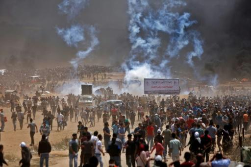 Palestinians run for cover from tear gas during clashes with Israeli security forces near the border between Israel and the Gaza Strip, east of Jabalia on May 14, 2018