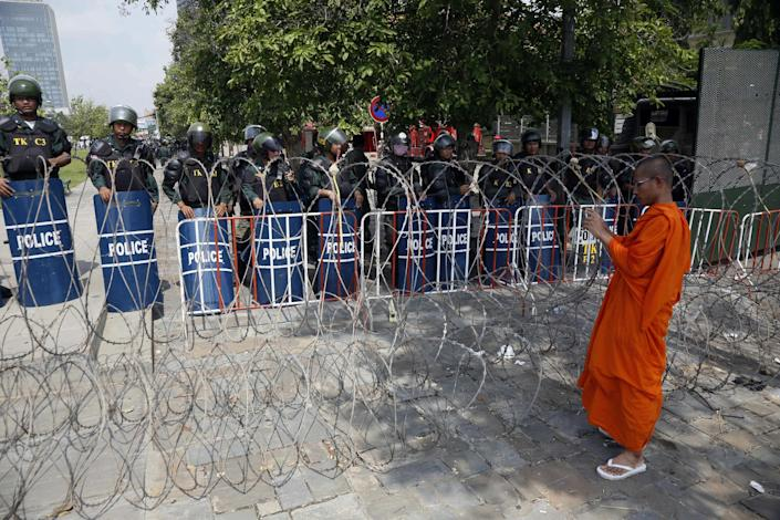 A Buddhist monk takes a photo of riot police standing at Freedom Park in Phnom Penh, Cambodia, Thursday, May 1, 2014. Security forces have beaten demonstrators after a May day rally held in defiance of a government ban on public protests in the Cambodian capital. Nearly 1,000 factory workers and supporters of the opposition Cambodia National Rescue Party had gathered on the streets outside the city's Freedom Park, which had been barred to demonstrators and sealed off. (AP Photo)