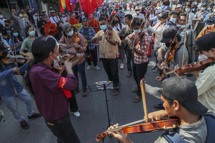 Anti-coup protesters play instruments and sing after riot policemen blocked their march in Mandalay, Myanmar, Wednesday, Feb. 24, 2021. Protesters against the military's seizure of power in Myanmar were back on the streets of cities and towns on Wednesday, days after a general strike shuttered shops and brought huge numbers out to demonstrate. (AP Photo)