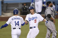Los Angeles Dodgers' Enrique Hernandez, from left to right, congratulates Corey Seager after Seager's two-run home run as Colorado Rockies catcher Elias Diaz looks on during the fifth inning of a baseball game in Los Angeles, Sunday, Sept. 6, 2020. (AP Photo/Kelvin Kuo)
