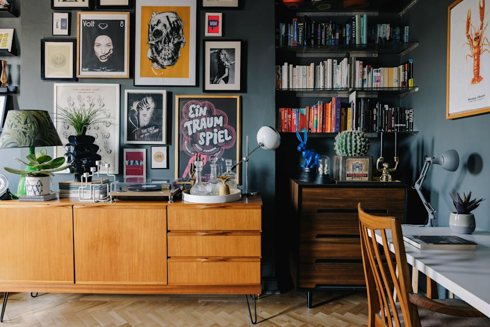 Dark matters: Farrow and Ball's Downpipe creates a moody backdrop for Alex Meachen's McIntosh teak sideboard and bright gallery wall (Mark Anthony Fox)