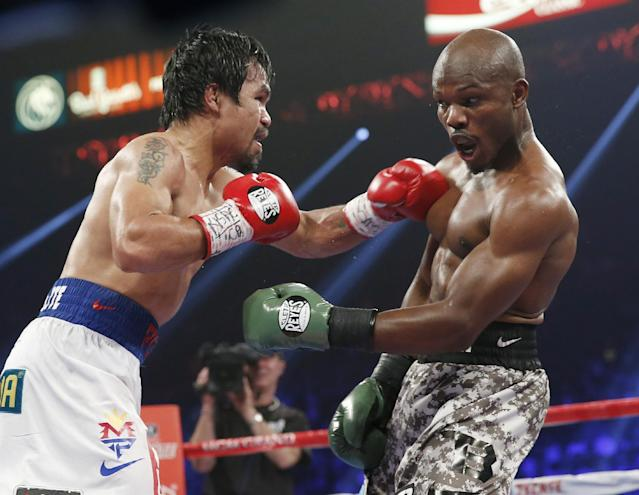 Manny Pacquiao, left, of the Philippines, throws a left at Timothy Bradley during the WBO welterweight title boxing bout Saturday, April 12, 2014, in Las Vegas. (AP Photo/Eric Jamison)