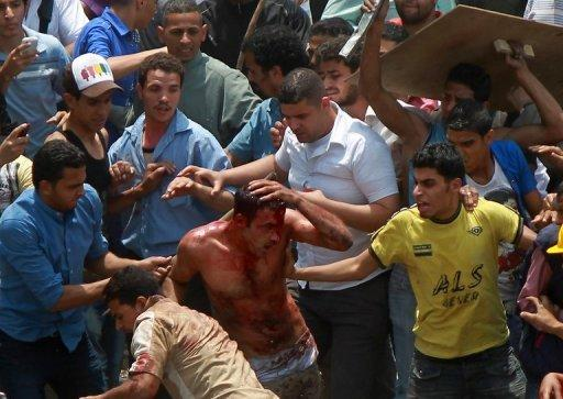 Egyptian protesters beat a man who they accused of attacking them in the Abbassiya district in Cairo