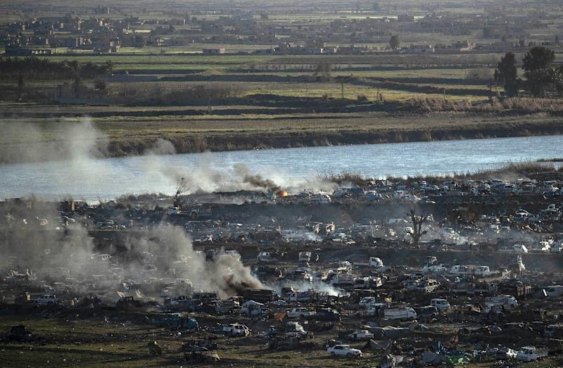 Smoke rises above the remains of the makeshift encampment on the north bank of the Euphrates River that had been the centre of the Islamic State group's last stand before it was overrun by the US-backed Syrian Democratic Forces earlier this week (AFP Photo/Delil SOULEIMAN)