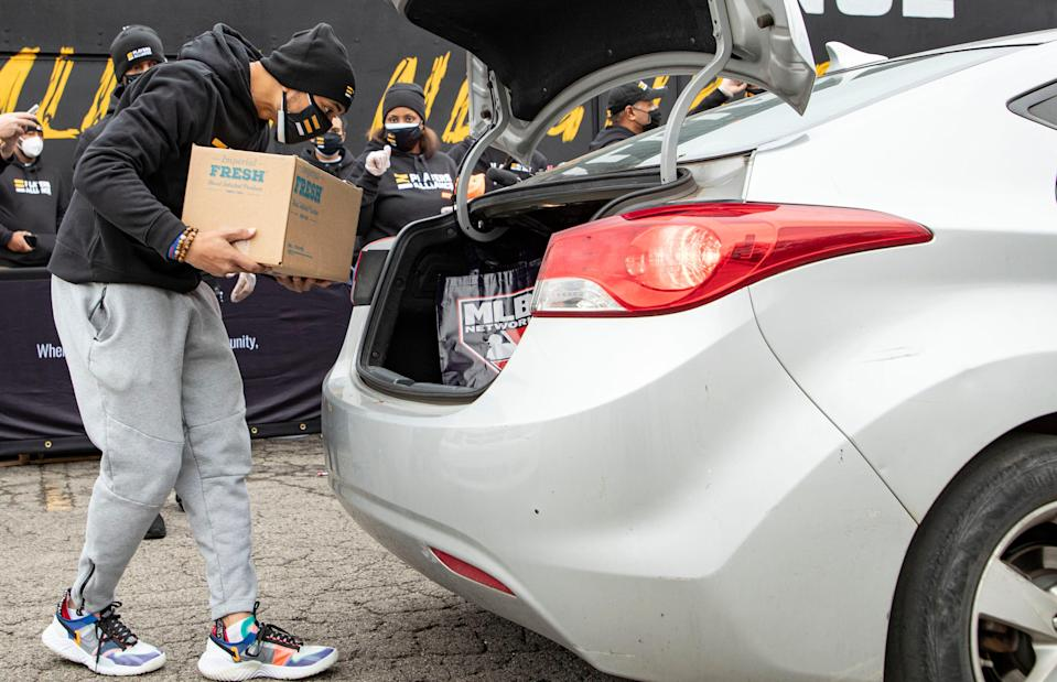 Los Angeles Dodgers star and Nashville native Mookie Betts loads a box of food into a car during A Pull Up Neighbor event at Pearl Cohn High School Saturday, Dec. 19, 2020, in Nashville, Tenn.