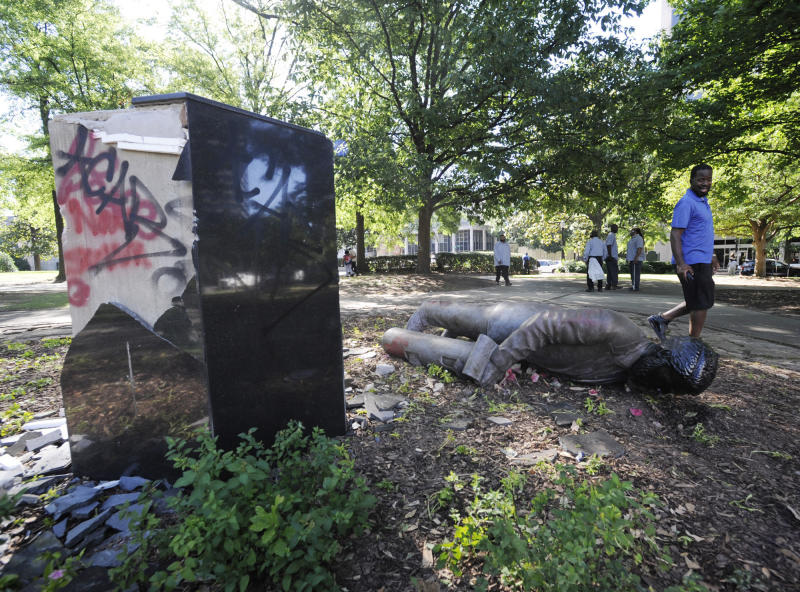 An unidentified man walks past a toppled statue of Charles Linn, a city founder who was in the Confederate Navy, in Birmingham, Ala., on Monday, June 1, 2020, following a night of unrest. (Jay Reeves/AP Photo)