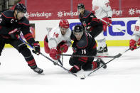 Carolina Hurricanes' Jordan Staal (11) and Brady Skjei (76) battle Detroit Red Wings' Robby Fabbri (14) for the puck during the first period of an NHL hockey game in Raleigh, N.C., Thursday, March 4, 2021. (AP Photo/Chris Seward)