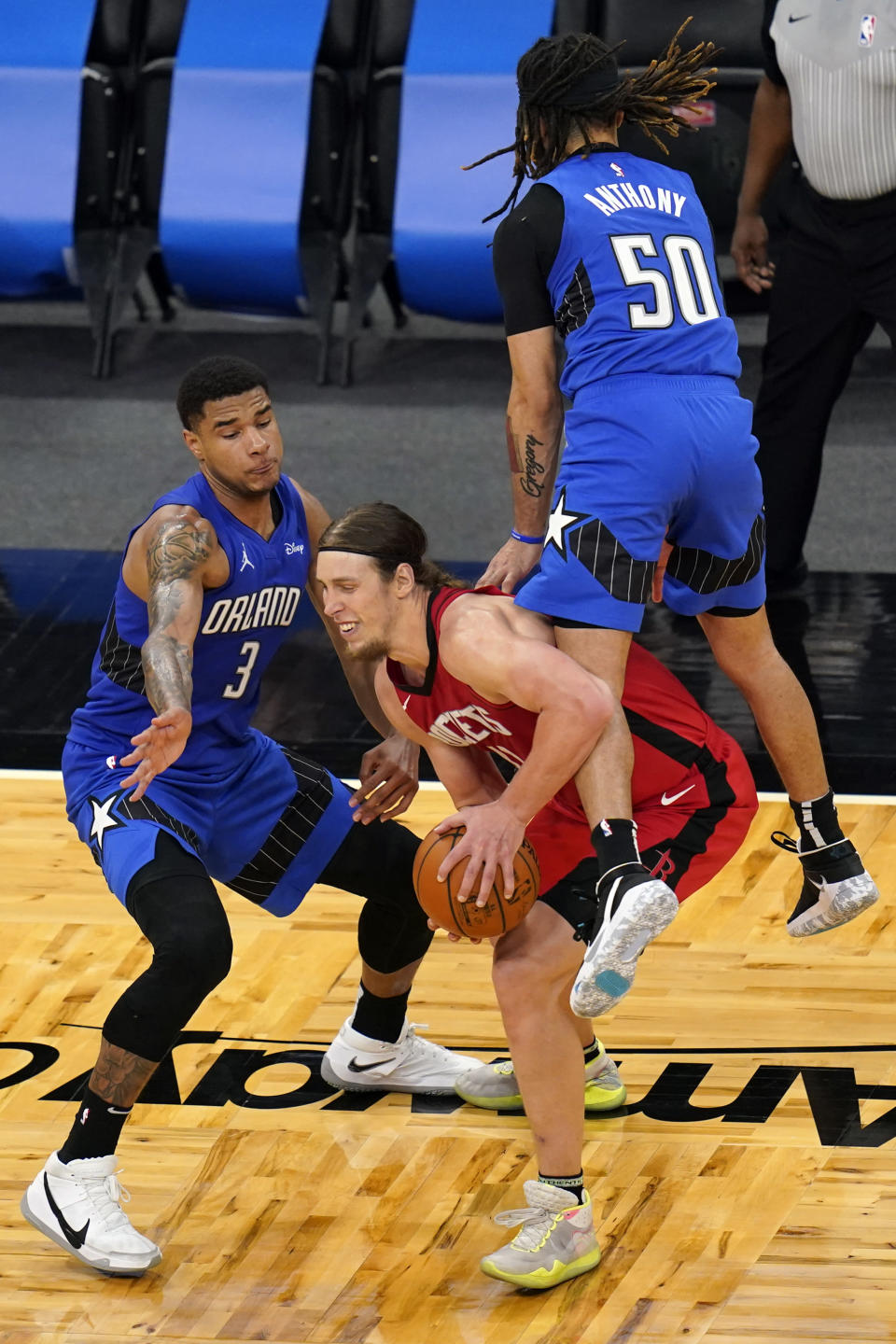 Orlando Magic guard Cole Anthony (50) fouls Houston Rockets forward Kelly Olynyk, center, in front of Orlando Magic forward Chuma Okeke (3) during the closing moments of the second half of an NBA basketball game, Sunday, April 18, 2021, in Orlando, Fla. (AP Photo/John Raoux)