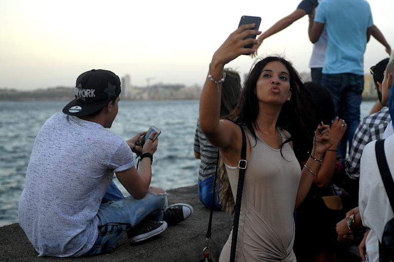 A young Cuban woman, part of a generation preparing for a future after the Castro brothers, is seen taking a selfie recently on Havana's Malecon esplanade (AFP Photo/Yamil LAGE)