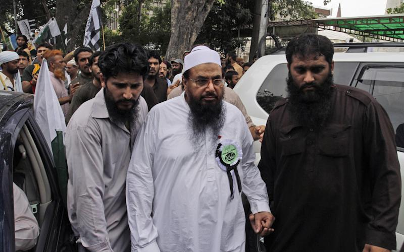 Hafiz Saeed, leader of Pakistani religious group Jamaat-ud-Dawa, center, is surrounded by guards as he arrives to attend a rally condemning the movement of NATO supplies to Afghanistan through Pakistan, in Lahore, Pakistan, Sunday, July 8, 2012. Prominent hardline Islamists led thousands of people in a protest against Pakistan's decision to allow the U.S. and other NATO countries to resume shipping troop supplies through the country to Afghanistan. (AP Photo/K.M. Chaudary)