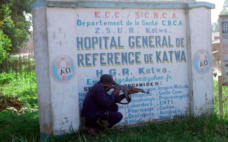 Police shelter behind a sign as they guard Butembo University Hospital, where a doctor was killed on Friday - AP