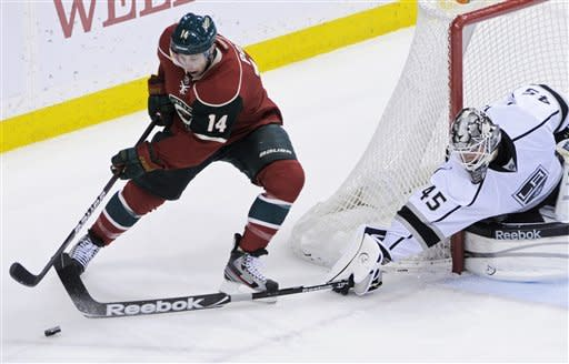 Los Angeles Kings goalie Jonathan Bernier, right, breaks up a scoring attempt by Minnesota Wild's Darroll Powe in the first period of an NHL hockey game Tuesday, Feb. 28, 2012 in St. Paul, Minn. (AP Photo/Jim Mone)
