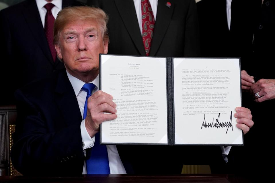 U.S. President Donald Trump holds his signed memorandum on intellectual property tariffs on high-tech goods from China, at the White House in Washington, U.S. March 22, 2018. REUTERS/Jonathan Ernst/File Photo