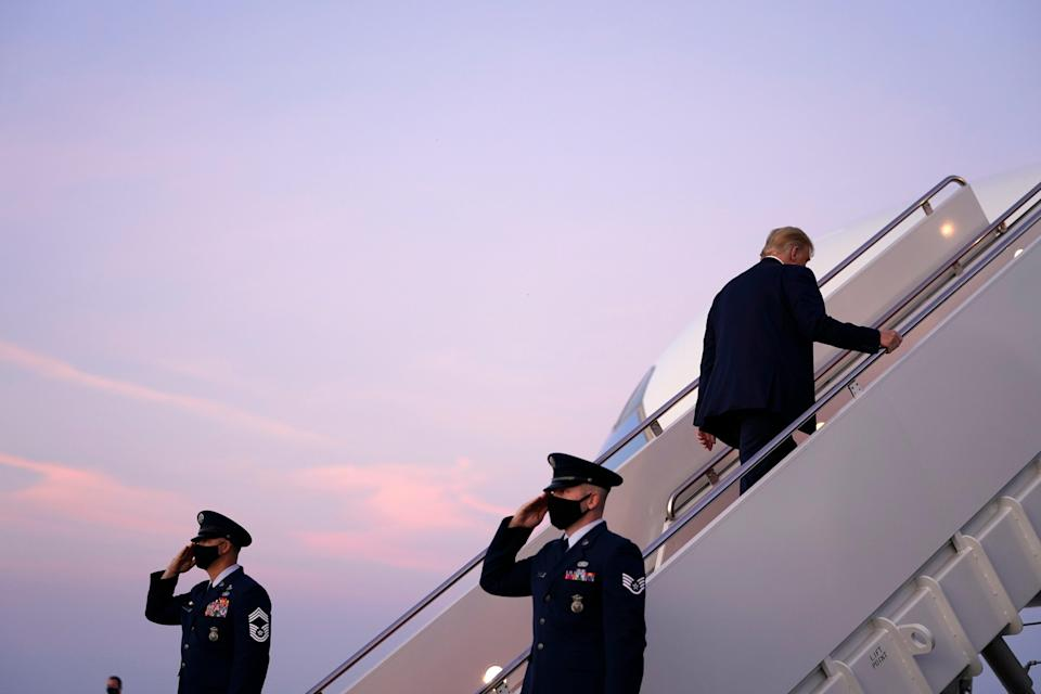 President Donald Trump boards Air Force One to travel to a campaign rally in Erie, Pennsylvania, amid a new row with