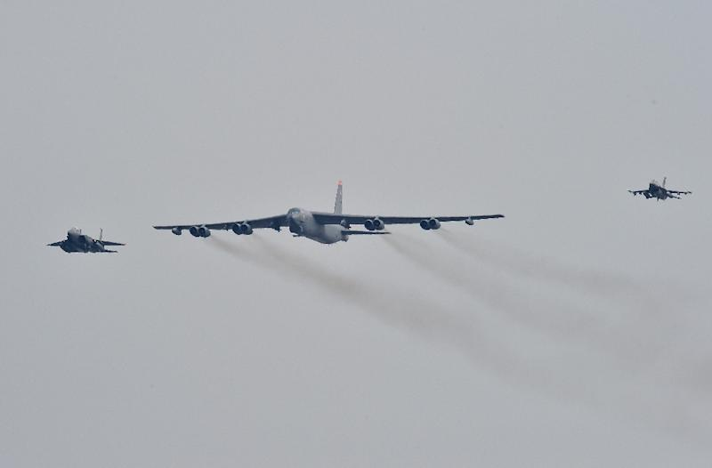 The US B-52 Stratofortress (C) was escorted by a South Korean F-15K fighter jet (L) and a US F-16 fighter jet (R) as it flew over the air base in Pyeongtaek, south of Seoul, on January 10, 2016 (AFP Photo/Jung Yeon-Je)