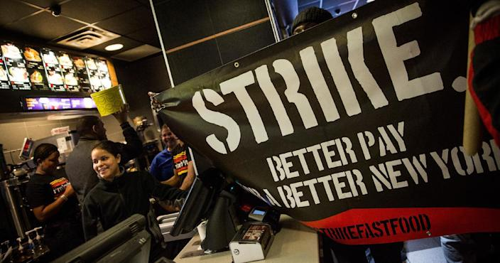 Protesters march through a McDonald's demanding a raise on the minimum wage to $15 per hour on December 4, 2014 in New York (AFP Photo/Andrew Burton)