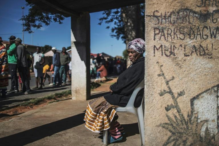 Informal traders and waste-pickers queue for food at a Soweto parking lot (AFP Photo/MARCO LONGARI)