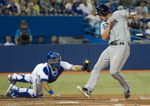 Tampa Bay Rays' Will Myers eludes the tag of Toronto Blue Jays catcher J.P. Arencibia to score during the ninth inning of a baseball game in Toronto on Friday, July 19, 2013. (AP Photo/The Canadian Press, Frank Gunn)