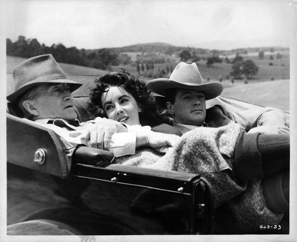 <p>Hudson, Taylor, and actor Paul Fix relaxed in a car on the set of <em>Giant</em>. </p>