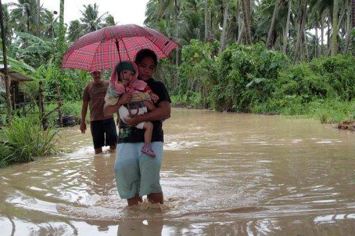 <p>A woman carrying her child wades through a flooded road brought about by heavy rains due to Typhoon Bopha, as she evacuates to a safer place, in Pantukan town on the southern island of Mindanao on December 4, 2012. Parts of Mindanao remained without power and communications, with food and clean water in limited supply after Bopha carved a path of destruction.</p>