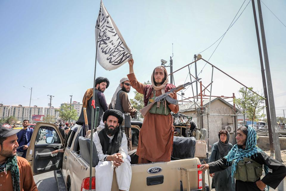 Taliban fighters are seen on the back of a vehicle in Kabul, Afghanistan, 16 August 2021. (Stringer/EPA-EFE/Shutterstock)