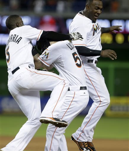 Miami Marlins' Adeiny Hechavarria, left, and Marcell Ozuna, right, mob Ed Lucas, center, after Lucas grounded into fielder's choice allowing Hechavarria to score the winning run in the 10th inning of a baseball game against the Washington Nationals, Saturday, July 13, 2013 in Miami. (AP Photo/Wilfredo Lee)