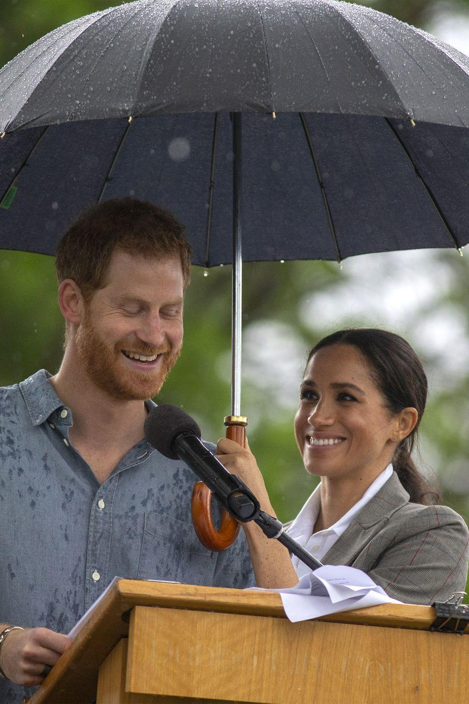 <p>Meghan has Harry's back, rain or shine! The duchess held an umbrella for Prince Harry as he made a speech during a Community Event at Victoria Park in Dubbo, Australia. </p>