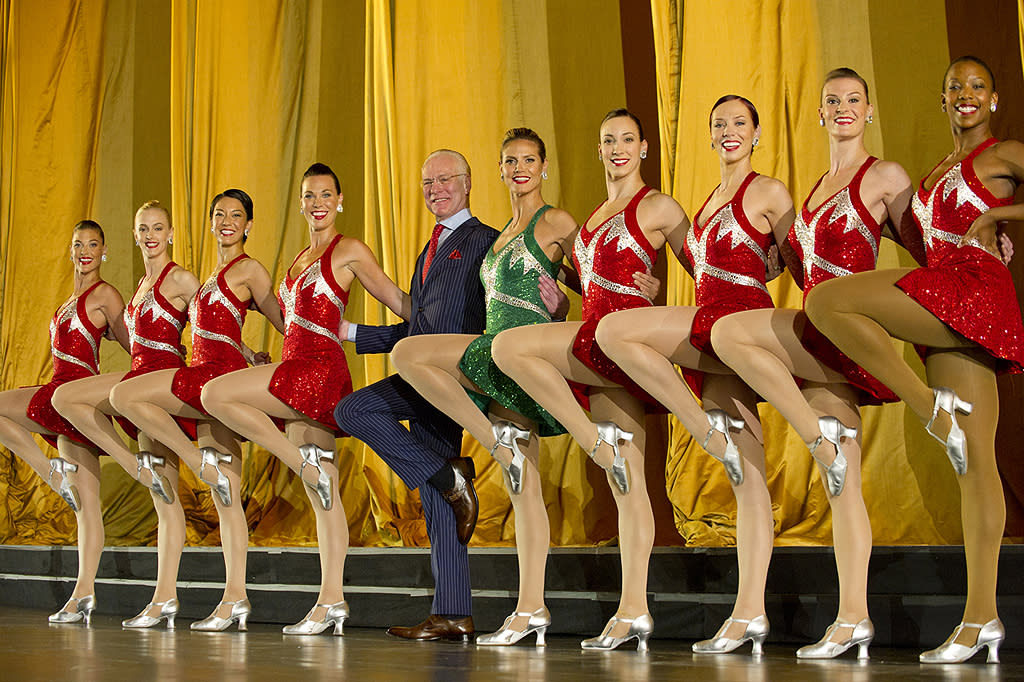 "Wow! Heidi Klum (in green) really looks like one of the Rockettes! Her ""Project Runway"" pal Tim Gunn, on the other hand? Not so much. The two hit Manhattan's Radio City Music Hall on Sunday while shooting an upcoming episode of their design-focused reality competition show. (7/8/2012)"