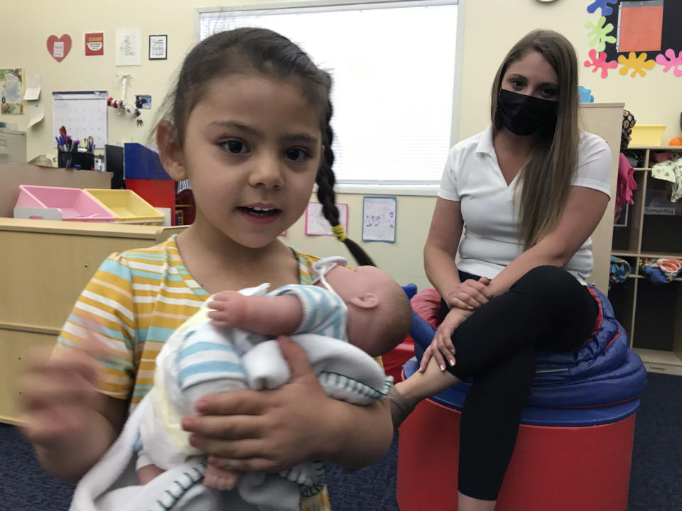 This May 4, 2021 image shows Arelyanna, 3, one of the students at Cuidando Los Ninos in Albuquerque, N.M., playing with a doll as child development director Paola Castillo supervises. The charity provides housing, child care and financial counseling for mothers, all of whom will benefit from expanded Child Tax Credit payments that will start flowing in July to roughly 39 million households. (AP Photo/Susan Montoya Bryan)