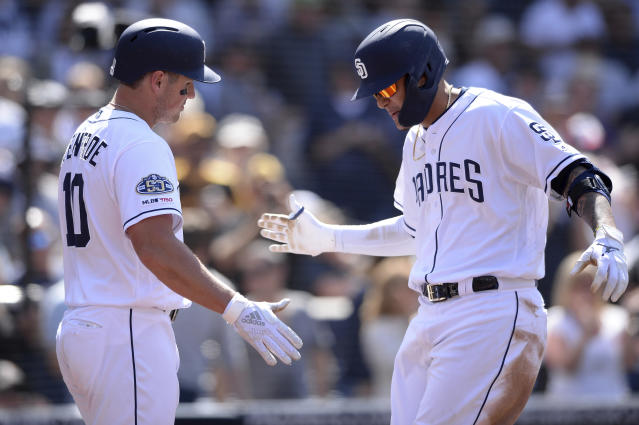 San Diego Padres' Manny Machado is congratulated by Hunter Renfroe after hitting a two-run home run during the seventh inning of a baseball game against the Arizona Diamondbacks Wednesday, April 3, 2019, in San Diego. (AP Photo/Orlando Ramirez)