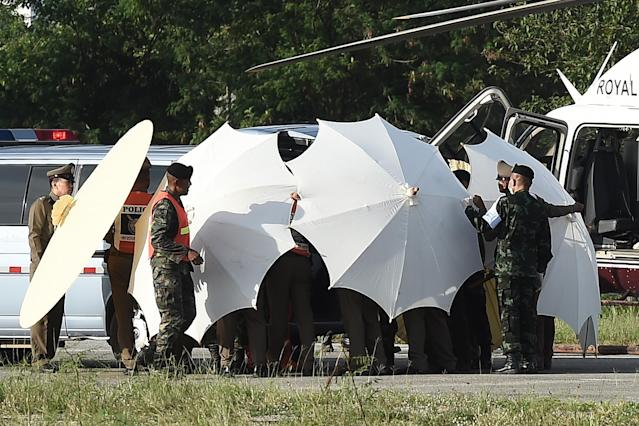 <p>Police and military personnel use umbrellas to cover a stretcher near a helicopter and ambulance at a military airport in Chiang Rai on July 9, 2018, as rescue operations continued for those still trapped inside the cave in Khun Nam Nang Non Forest Park in Thailand. (Photo: Lillian Suwanrumph/AFP/Getty Images) </p>