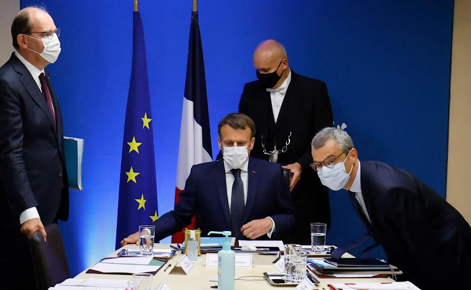 French President Emmanuel Macron (C) flanked by French Prime Minister Jean Castex (L) and Secretary General of the Elysee Palace Alexis Kohler (R) starts a national security meeting to discuss Pegasus spyware in the Jupiter room at The Elysee Presidential Palace in Paris, France, 22 July 2021 (EPA)