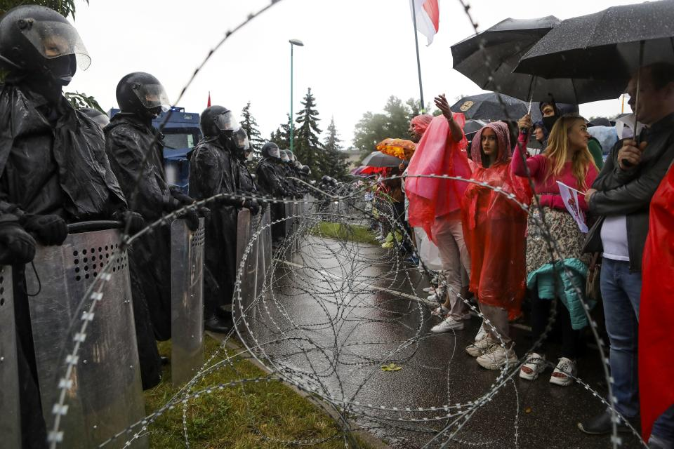 Protesters argue with police standing in front of a police barricade blocking opposition rally from moving toward the Independence Palace, residence of the President Alexander Lukashenko in Minsk, Belarus, Sunday, Sept. 6, 2020. Sunday's demonstration marked the beginning of the fifth week of daily protests calling for Belarusian President Alexander Lukashenko's resignation in the wake of allegedly manipulated elections. (AP Photo)