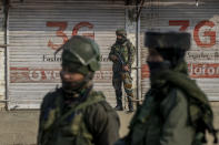 Indian army soldiers look towards the site of a gun battle on the outskirts of Srinagar, Indian controlled Kashmir, Wednesday, Dec. 30, 2020. A gun battle between rebels and government forces overnight killed three rebels on the outskirts of Srinagar on Wednesday, officials said. (AP Photo/ Dar Yasin)